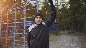 Jonge atletenmens die vóór training opleiding in de winterpark opwarmen Stock Foto's