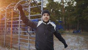 Jonge atletenmens die vóór training opleiding in de winterpark opwarmen Stock Fotografie