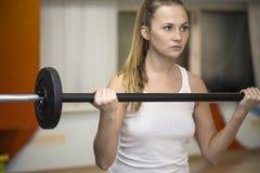 Jonge atletenvrouw die met barbell uitoefenen stock foto