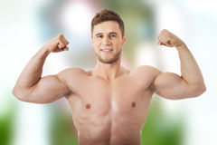 Jonge atletische mens die zijn spieren tonen stock fotografie