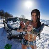 Jonge atletische vrouw die auto in de winter trekken royalty-vrije stock afbeelding