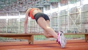Jonge atletische vrouw die haar benen opleiden die een bank gebruiken stock footage