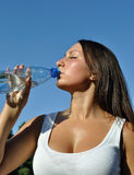 Jonge atletische vrouw die koud water drinkt Stock Foto