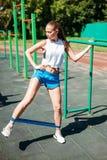 Jonge atletische vrouw die oefeningen met elastiek doen stock foto's
