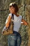 Jonge, atletische vrouw in jeans met handtas. stock foto's