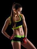Jonge atletische vrouw in sportkleding het stellen in studio tegen zwarte achtergrond Ideaal vrouwelijk sportencijfer Royalty-vrije Stock Afbeelding