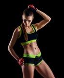 Jonge atletische vrouw in sportkleding het stellen in studio tegen zwarte achtergrond Ideaal vrouwelijk sportencijfer Stock Foto's