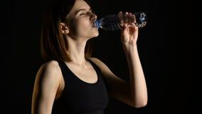 Jonge atletische vrouw in sportkledings drinkwater in studio tegen zwarte achtergrond Ideaal vrouwelijk sportencijfer stock videobeelden
