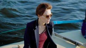 Jonge attrative roodharige vrouwenzitting op het schipdek die van het ogenblik van de afgelopen zomer dag genieten stock footage