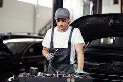 Jonge automechanic wordt geconcentreerd op het proces om een auto te herstellen stock afbeeldingen