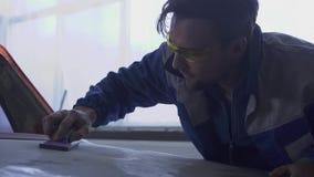 Jonge autospecialist die de kap van de auto met speciale glazen oppoetsen en eenvormig in de moderne autodienst stock video