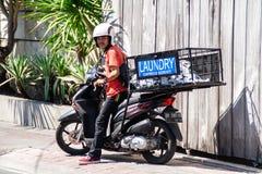 Jonge Aziaat die als kerel van de wasserijlevering in Bali werken stock afbeeldingen