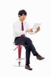 Jonge Aziatische bedrijfsmens die een zitting van stootkussenPC op de stoel gebruiken. Royalty-vrije Stock Afbeelding