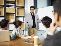 Jonge Aziatische bedrijfspersoon die een bespreking vergemakkelijken stock afbeelding