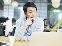 Jonge Aziatische bedrijfspersoon die hard in bureau denkt Royalty-vrije Stock Afbeeldingen