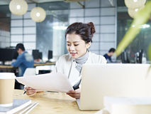 Jonge Aziatische bedrijfsvrouw die in bureau werken Royalty-vrije Stock Afbeeldingen