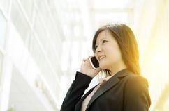 Jonge Aziatische bedrijfsvrouw die op mobiele telefoon spreken Royalty-vrije Stock Afbeelding