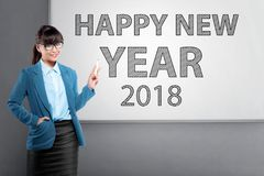 Jonge Aziatische bedrijfsvrouw die zich met Gelukkige Nieuwjaar 2018 tex bevinden Stock Fotografie