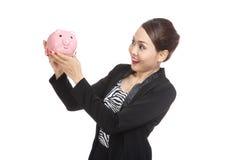 Jonge Aziatische bedrijfsvrouw met een bank van het varkensmuntstuk Stock Fotografie