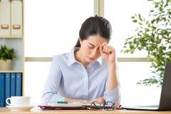 Jonge Aziatische bedrijfsvrouw met hoofdpijn stock afbeelding