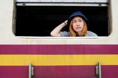 Jonge Aziatische blonde haarvrouw die uit het venster kijken Stock Foto