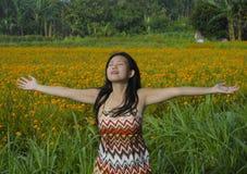 Jonge Aziatische Chinese toeristenvrouw die ontspannen openend haar wapens vrij om de mening van een mooi landschap van het bloem Royalty-vrije Stock Foto's