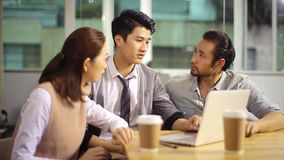 Jonge Aziatische collectieve stafmedewerkers die zaken in bureau bespreken stock footage