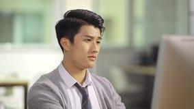 Jonge Aziatische directeur die in bureau werken stock footage