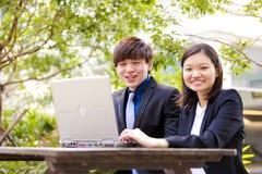 Jonge Aziatische directeuren in bespreking die lijstpc met behulp van Stock Foto's