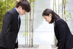 Jonge Aziatische directeuren die aan elkaar buigen Stock Foto
