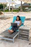 Jonge Aziatische freelancer die aan laptop bij het strand werken stock foto