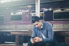 Jonge Aziatische hipstermens die mobiele telefoon houden die app lied gebruiken met Stock Afbeelding