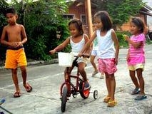 Jonge Aziatische jonge geitjes die en een fiets spelen berijden royalty-vrije stock fotografie