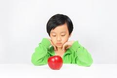 Jonge Aziatische jongen aarzelend om gezond voedsel te eten royalty-vrije stock afbeeldingen