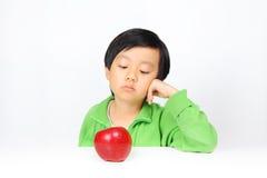 Jonge Aziatische jongen aarzelend om gezond voedsel te eten stock afbeeldingen