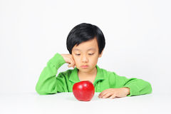 Jonge Aziatische jongen aarzelend om gezond voedsel te eten stock foto's