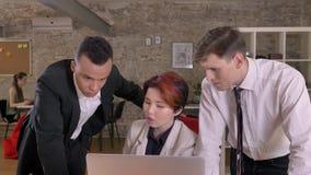 Jonge Aziatische, Kaukasische en zwarte bedrijfsmensen die en over laptop in modern bureau bespreken plannen stock video