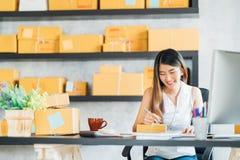 Jonge Aziatische kleine bedrijfseigenaar die thuis bureau werken, die nota nemen aan kooporders Marketing online verpakkingslever
