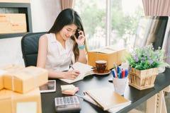 Jonge Aziatische kleine bedrijfseigenaar die thuis bureau werken, mobiele telefoon met behulp van en nota nemen op kooporders stock afbeelding