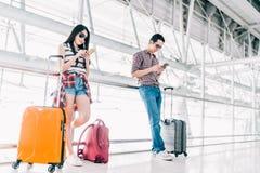 Jonge Aziatische man en vrouw die smartphone gebruiken die vlucht of online controle bij luchthaven samen, met bagage controleren stock afbeeldingen