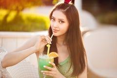 Jonge Aziatische maniervrouw het drinken cocktail in een strandbar stock afbeelding