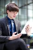 Jonge Aziatische mannelijke directeur die tabletpc met behulp van Stock Foto