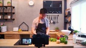 Jonge Aziatische mens in de video van de keukenopname op camera Glimlachende Aziatische mens die aan voedsel blogger concept werk stock footage
