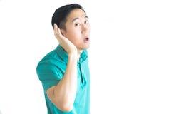 Jonge Aziatische mens die aan iets proberen te luisteren royalty-vrije stock fotografie