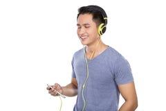 Jonge Aziatische mens die aan muziek met een hoofdtelefoon luisteren stock afbeeldingen