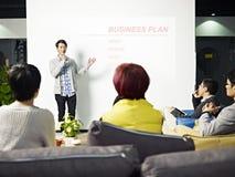 Jonge Aziatische mens die businessplan voorleggen stock afbeeldingen