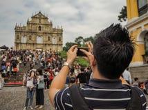 Jonge Aziatische mens die een beeld van de Ruïnes van St Paul in een grote massa van Chinese toeristen nemen stock foto