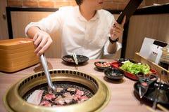 Jonge Aziatische mens die Koreaans Barbecuebuffet in restaurant eten stock foto