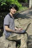 jonge Aziatische mens die laptop met behulp van Royalty-vrije Stock Fotografie