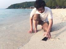 Jonge Aziatische mens die mobiele slimme telefoon op tropisch zandig strand laten vallen Ongeval en van het verzekerings elektron royalty-vrije stock afbeelding